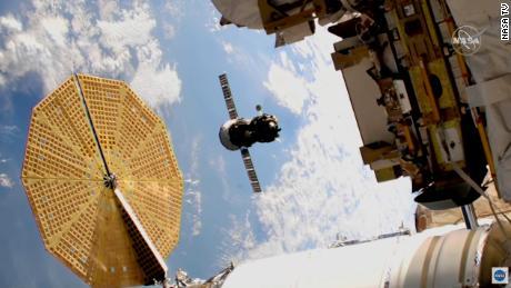 Das Sojus-Raumschiff ist in der Mitte dieses Bildes im Flug zu sehen.