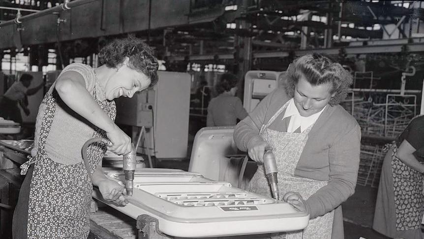 Schwarz-Weiß-Foto von zwei Frauen, die 1956 in einer Emmco-Fabrik durch Kühlschranktüren graben.