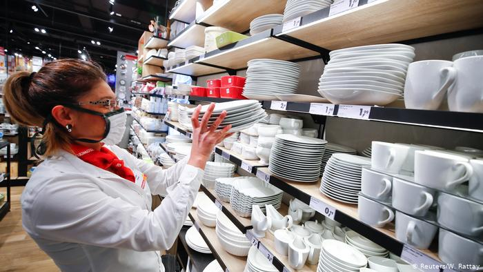 Eine Mitarbeiterin eines Möbelhauses im nordrhein-westfälischen Pulheim trägt eine Maske, während sie Produkte in einem Regal anordnet.  In mehreren Bundesländern wurde die Pflicht zum Tragen eines Mundschutzes eingeführt, um die Ausbreitung des Coronavirus einzudämmen.
