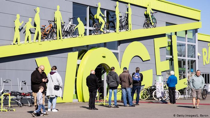 Radfahrer stellen sich vor einem Fahrradladen in Dinslaken, Nordrhein-Westfalen, auf, nachdem dieser nach der Sperrung des Coronavirus in Deutschland wiedereröffnet wurde.  Fahrradgeschäfte, Buchhandlungen und Autohändler dürfen bundesweit wieder öffnen.