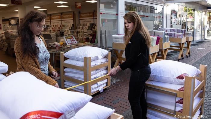 Zwei Mitarbeiter eines Stores im nordrhein-westfälischen Dinslaken bestimmen, wo Kunden stehen können, um soziale Distanzierung zu gewährleisten.  Der Laden wird nach der Schließung des Coronavirus in Deutschland wiedereröffnet.